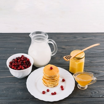 Stacked of pancakes; red currant berries; milk and lemon curd on black wooden background