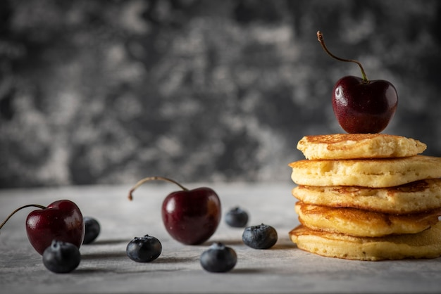 Stacked pancakes with cherries and blueberries on a vintage gray wooden table space for text