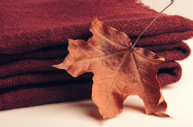 Stacked pile of burgundy knitted plaid on white background with an autumn sheet of maple