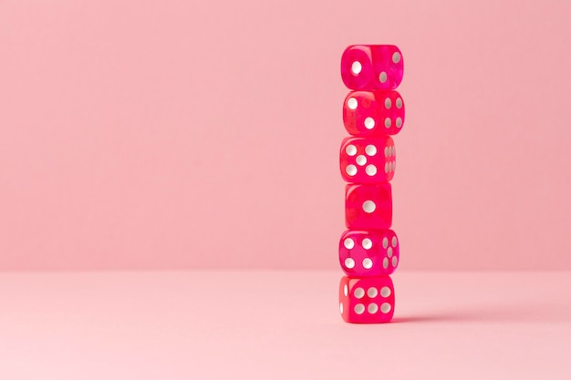 Stacked pink dices on pink background