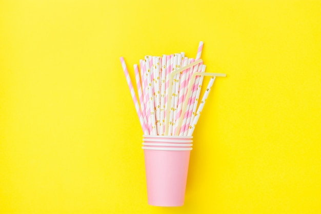 Stacked pink drinking paper cups with striped straws on yellow background.