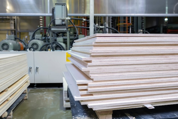 Stacked plywood and wooden board products against de-focused blurred piece of industrial warehouse