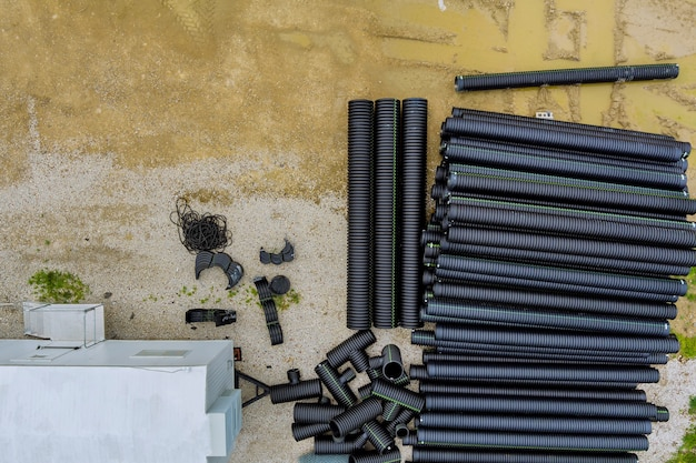 신축 건물에 임시로 쌓인 검은색 플라스틱 더미의 폴리에틸렌 파이프