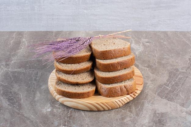 Fette impilate di pane integrale e un gambo di grano viola su un vassoio su sfondo marmo. foto di alta qualità