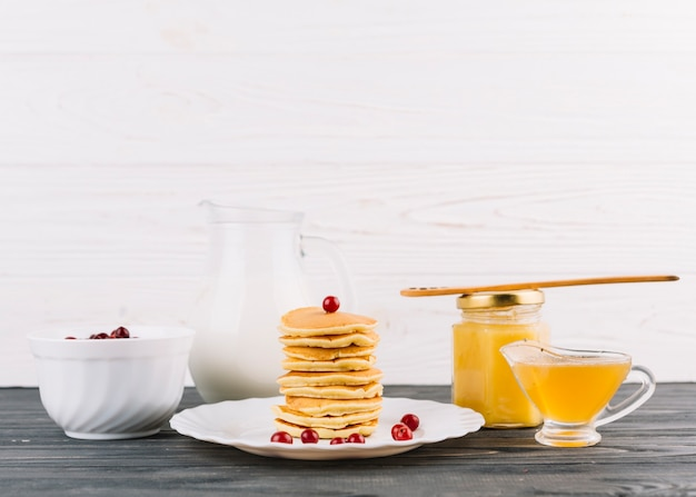 Stacked of small pancakes with red currant berries and lemon curd against white wall