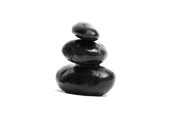 Уложены гладкие черные камни. морская галька. балансировка мокрой галькой на белом фоне