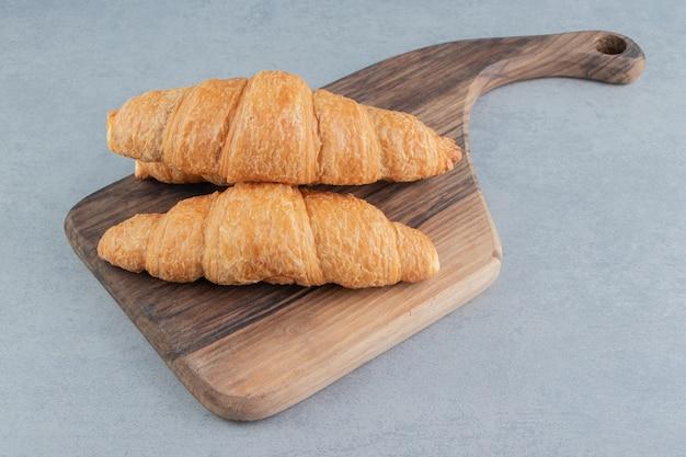 Impilati uno sopra l'altro croissant su sfondo blu. foto di alta qualità