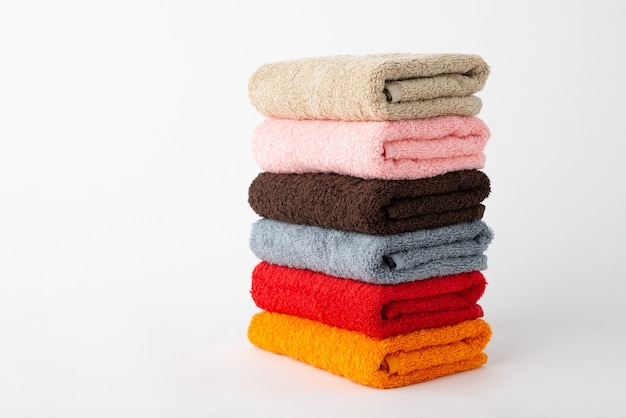 Stacked towels of different colour on a grey background