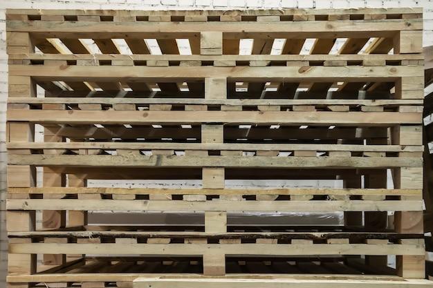Штабелированные использованные деревянные поддоны на складе. штабели грузовых поддонов европейского типа. фон из деревянных поддонов. концепция складирования и хранения товаров