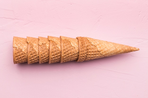 Stacked waffle cones on pink background