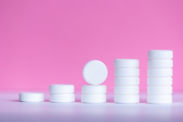 Stacked white pills on pink, growing pharm business concept