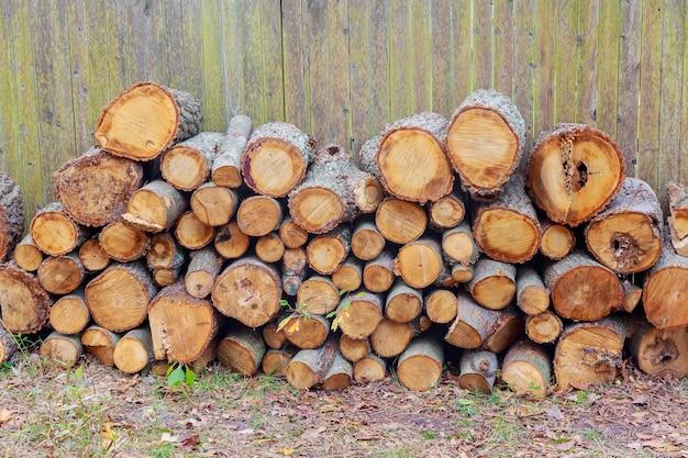 積み重ねられた木は背景の木の丸いパターン、織り目加工、材木、材料を切りました