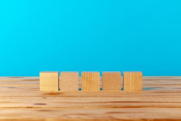 青い背景、コピースペースに対して木製の机の上に積み上げられた木製のブロック