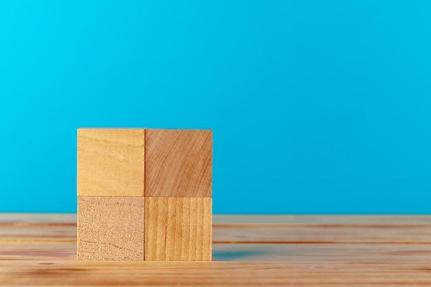 青い背景に対して木製の机の上に積み上げられた木製のブロック