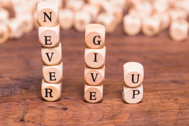 Stacked of wooden blocks with word never give up on wooden desk