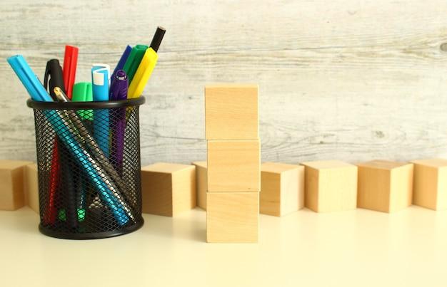 질감 있는 회색 배경에 흰색 작업 테이블에 편지를 위한 누적된 나무 큐브. 비즈니스 개념