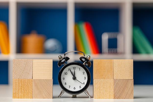目覚まし時計とテーブルの上に積み上げられた木製の立方体