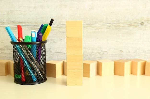 질감 있는 회색 배경의 흰색 작업 테이블에 빈 공간이 있는 쌓인 나무 큐브.