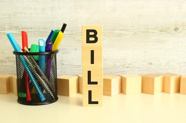 질감 있는 회색 배경에 흰색 작업 테이블에 bill이라는 글자가 있는 쌓인 나무 큐브. 비즈니스 개념