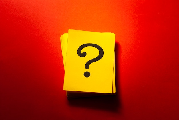 Stacked yellow cards with printed question mark