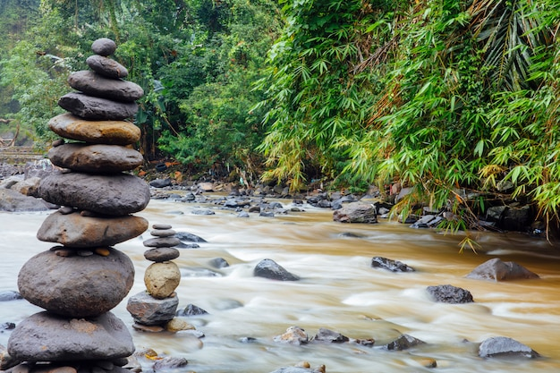 Stacked zen stones at tegenungan waterfall at bali, indonesia