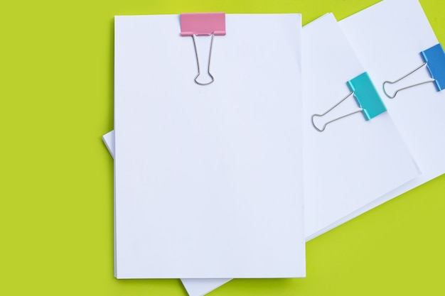 Stacking of business document with colorful binder clips on green background.