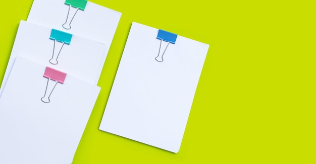 Stacking of business document with colorful binder clips on green surface
