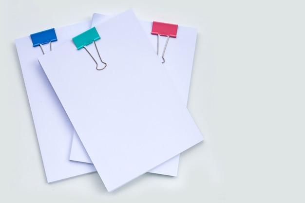 Stacking of business document with colorful binder clips on white surface