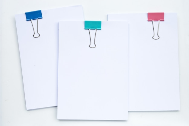 Stacking of business document with colorful binder clips on white