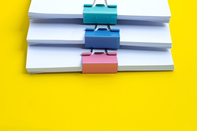 Stacking of business document with colorful binder clips on yellow surface