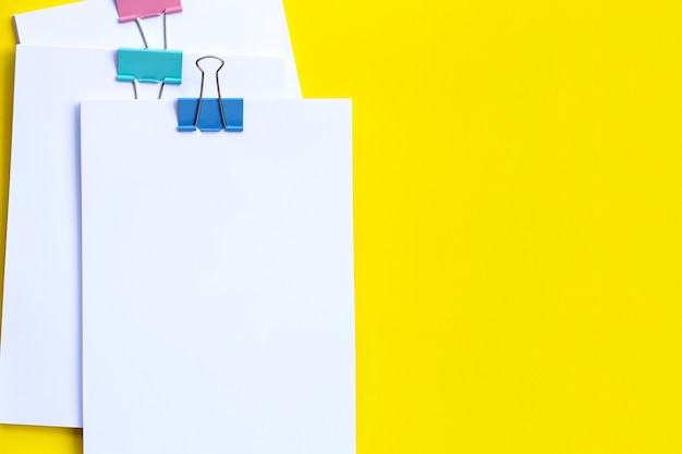 Stacking of business document with colorful binder clips on yellow