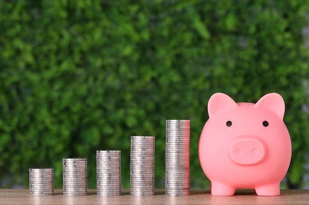 Укладка монеты, растущей с розовой копилкой на фоне зеленой природы