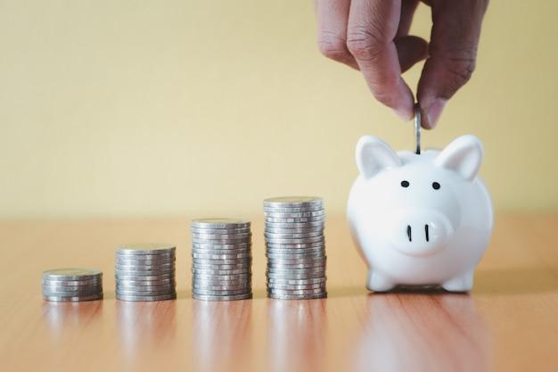 コインを積み重ねて手でコインを白い貯金箱に入れてお金を節約し、成長へのステップアップを計画し、退職基金と将来の計画のコンセプトのためにお金を節約します。