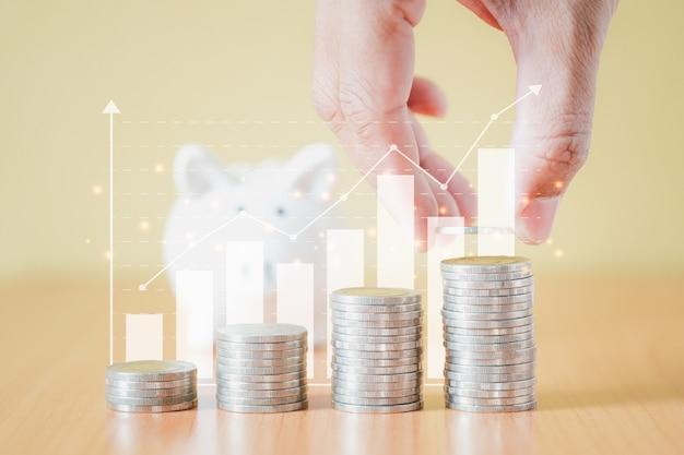 스택 동전 더미와 손을 돈으로 저축에 대 한 비즈니스 그래프 배경으로 흰색 돼지 저금통에 동전을 넣어 성장 하 고, 미래 계획 개념에 대 한 돈을 절약하는 단계까지.