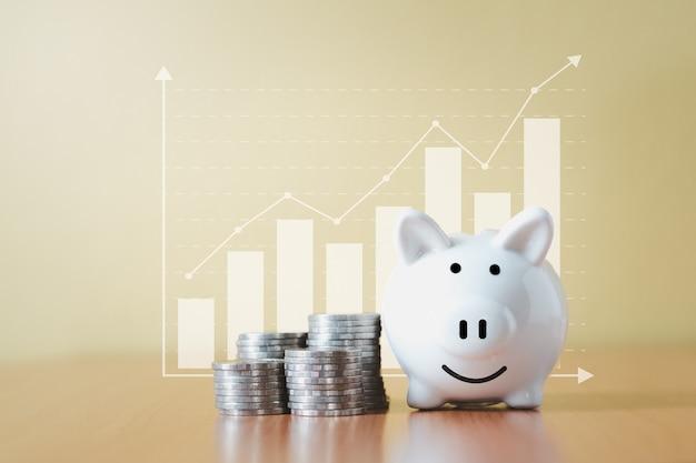 스택 동전 더미와 돈으로 저축을위한 흰색 돼지 저금통 및 계획 단계는 비즈니스 그래프 배경으로 성장하고 퇴직 기금 및 미래 계획 개념에 대한 비용을 절약합니다.