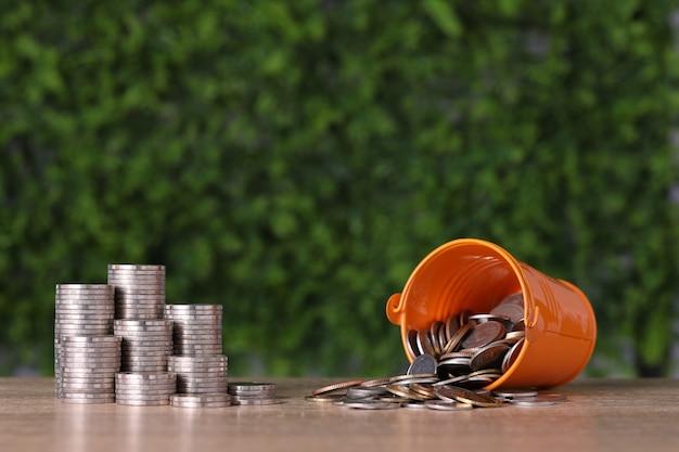 Укладка монет сберегает рост с нержавеющей чашкой, заполненной монетами на деревянном столе и зеленом фоне.