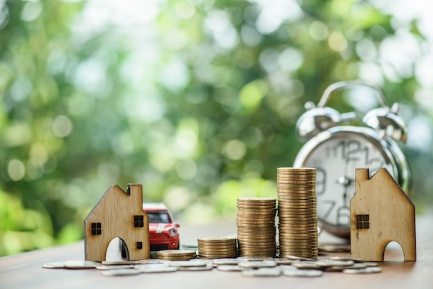 Stacking dollars coins with a house and car model.save and investment for buy house concept .for the