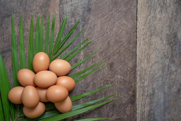 木製の背景に対してヤシの葉に卵を積み重ねる
