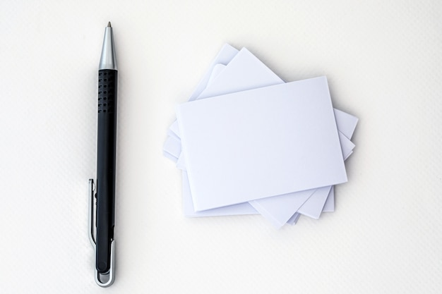 Stacking of mockup empty white business card with elegance pen  on a white paper background