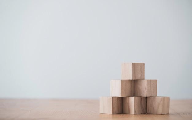 Укладка пустых деревянных кубиков на стол с копией пространства для ввода текста и значка инфографики.