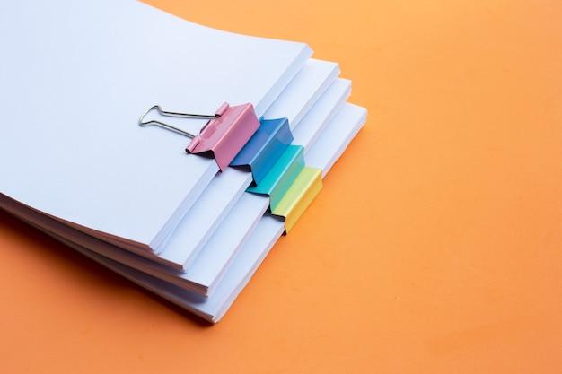 オレンジ色の背景にカラフルなバインダークリップとビジネスドキュメントの積み重ね。コピースペース