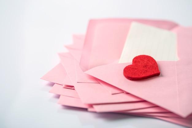 ピンクの封筒と郵便手紙と赤い目隠しの積み重ね