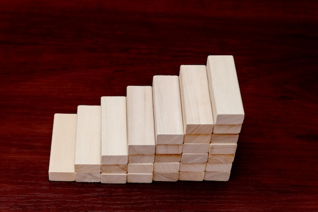 Stacking wooden blocks in shape of staircase.  ladder career path concept for business growth success process.