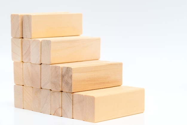 Stacking wooden blocks in shape of staircase on white wall.  ladder career path concept for business growth success process.