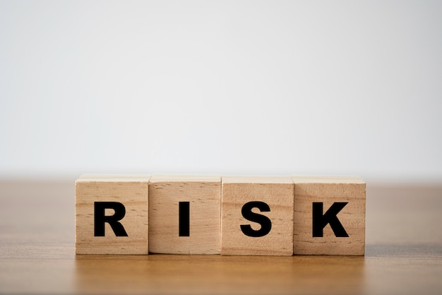 Stacking of wooden which print screen risk wording on the table with copy space. risk management concept.