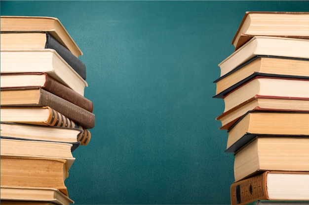 Stacks of books with green chalk board on background