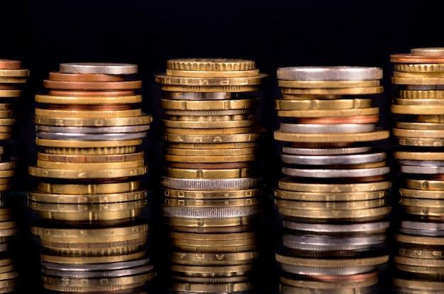 黒の背景にさまざまな国のコインを積み重ねます。