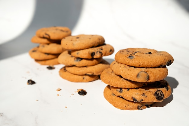 Stacks of chocolate chip cookies with pieces of chocolate on marble background
