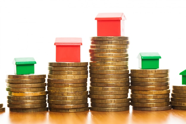 Stacks of coins, green and red home, mortgage concept by money house from coins