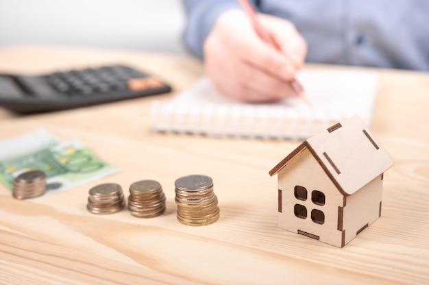 電卓で木製のテーブルにコインを積み重ねます。毎月の住宅費を計算する計算機を使用している男